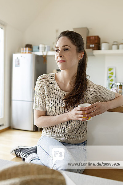 Young woman with cup of coffee relaxing in kitchen