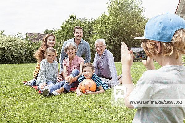 Junge fotografiert glückliche Großfamilie im Garten