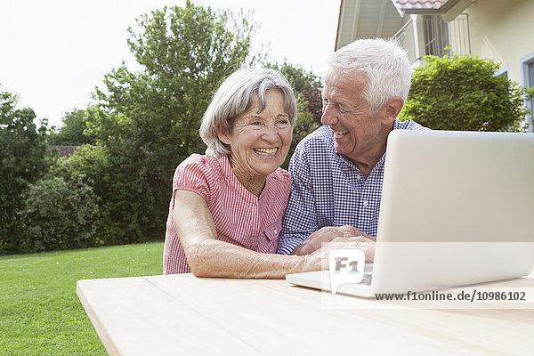Glückliches Seniorenpaar mit Laptop im Garten