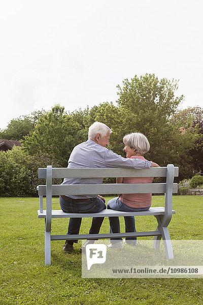 Glückliches Seniorenpaar sitzt auf der Bank im Garten