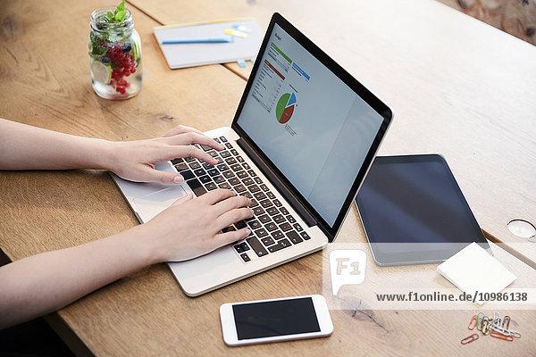 Frau am Schreibtisch mit Laptop bei der Kalkulation