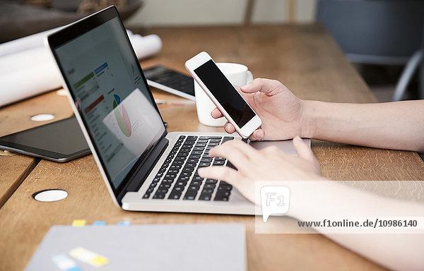 Frau am Schreibtisch mit Laptop und Smartphone bei der Kalkulation