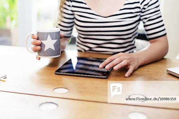 Nahaufnahme einer Frau  die eine Tasse Kaffee mit Hilfe eines digitalen Tabletts hält.