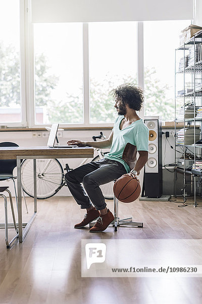 Junger Mann spielt mit Basketball im Büro