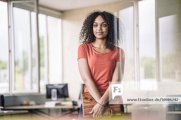 Junge Frau im Büro mit Laptop