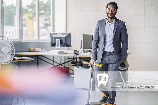 Young businessman with kickboard in office
