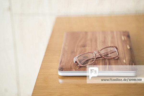 Holz-Laptop und Holzgläser auf dem Schreibtisch