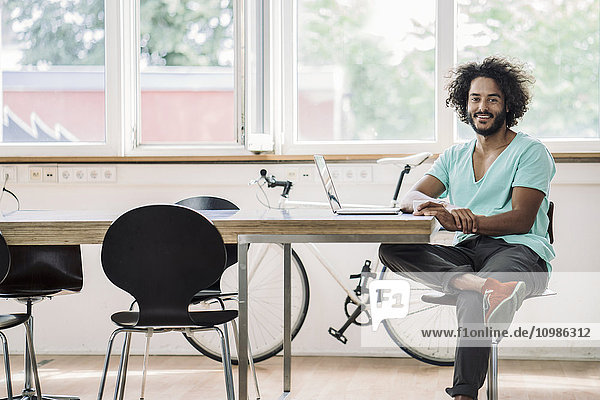 Young designer sitting in office using laptop