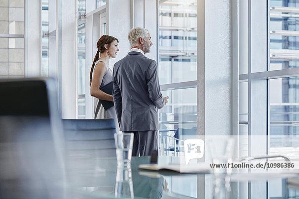 Zwei Geschäftsleute  die aus dem Fenster schauen.