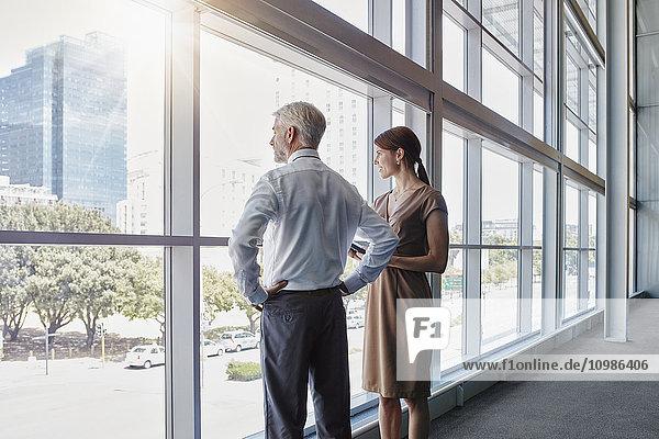 Zwei Geschäftsleute  die aus einem großen Fenster schauen.