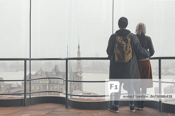 Belgien  Antwerpen  Rückansicht des Paares mit Blick durchs Fenster auf die Hafengebiete