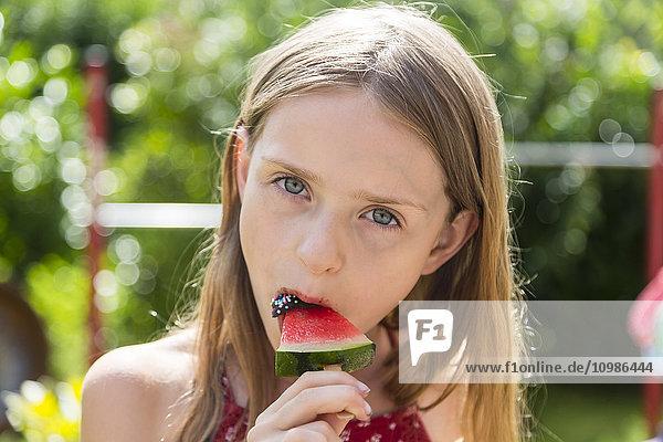 Porträt eines Mädchens  das eisgekühlte Wassermelone isst. Porträt eines Mädchens, das eisgekühlte Wassermelone isst.