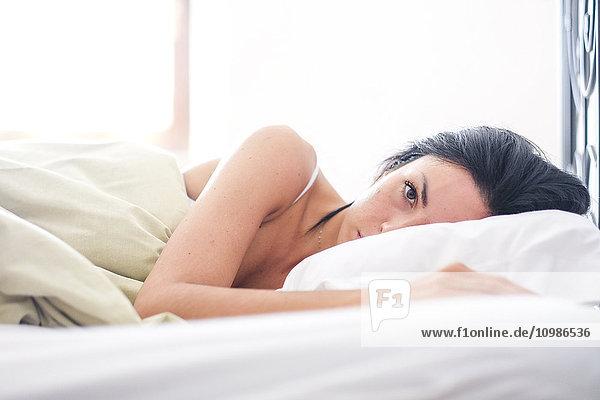 Frau auf dem Bett liegend  aufwachend