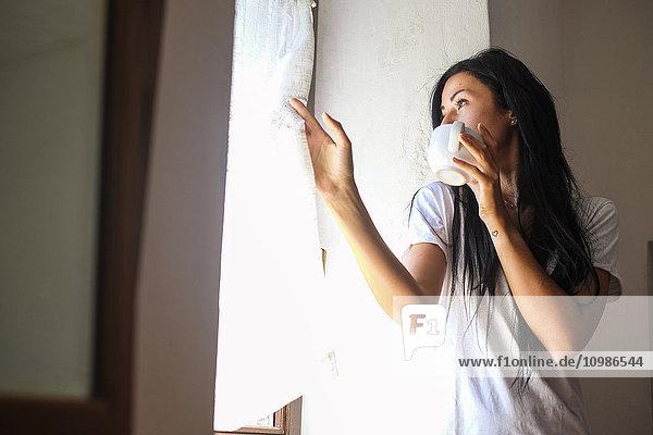 Woman drinking coffee  looking through window