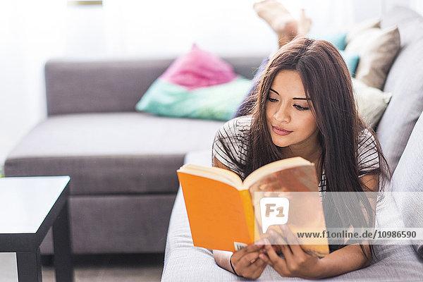 Teenagermädchen liegt auf der Couch und liest ein Buch.