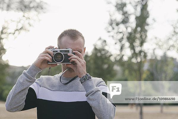 Mann fotografiert mit Vintage-Kamera