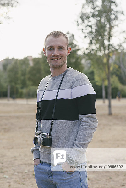 Portrait of smiling man with vintage camera