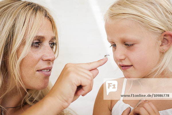Little girl watching fly sitting on her mother's finger