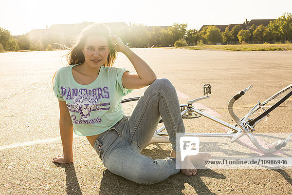 Lächelnde junge Frau mit Fahrrad im Gegenlicht sitzend