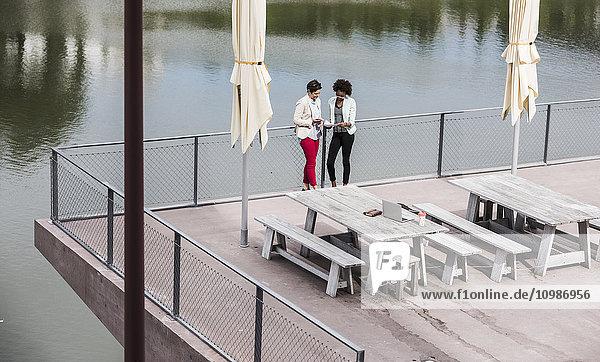 Zwei Geschäftsfrauen  die auf der Terrasse stehen und Dokumente von oben betrachten.