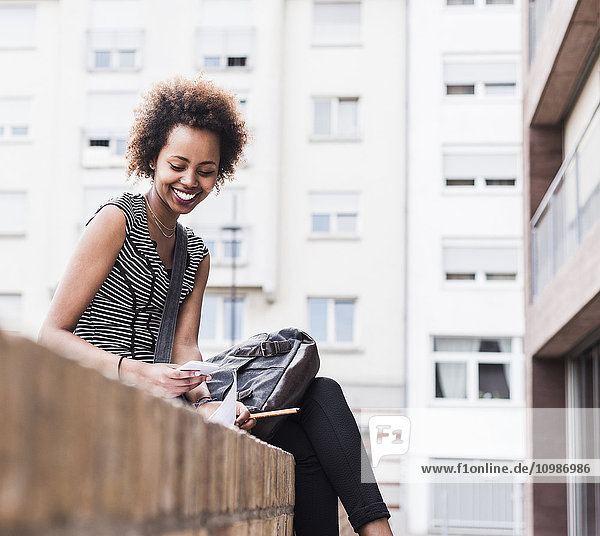 Smiling youngbusiness woman sitting on wall looking at cell phone