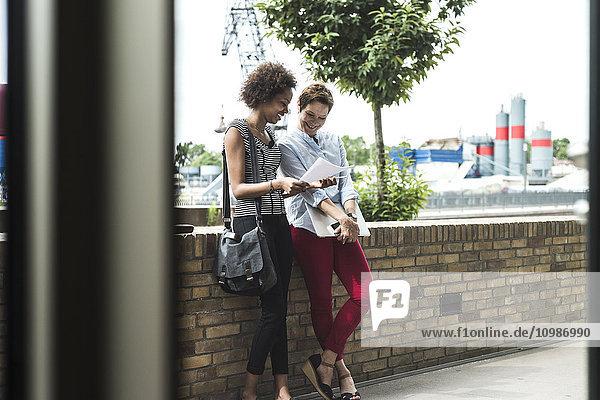 Zwei Geschäftsfrauen  die Seite an Seite stehen und Dokumente betrachten
