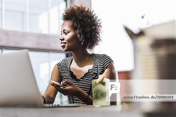 Geschäftsfrau mit Smartphone und Laptop im Bürgersteigcafé
