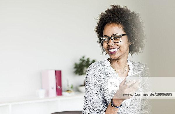 Porträt einer lächelnden Geschäftsfrau mit Brille im Büro
