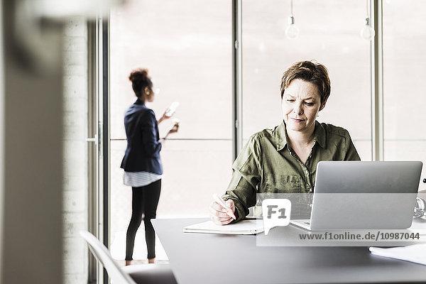 Geschäftsfrau sitzt am Schreibtisch und schreibt etwas auf.