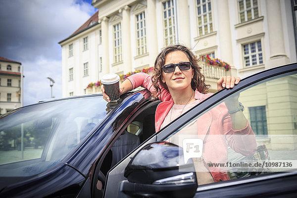Porträt einer Frau mit Sonnenbrille auf dem Auto