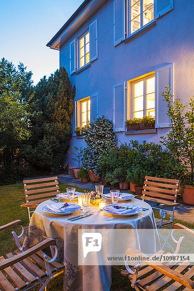Gedeckter Tisch im Garten am Abend
