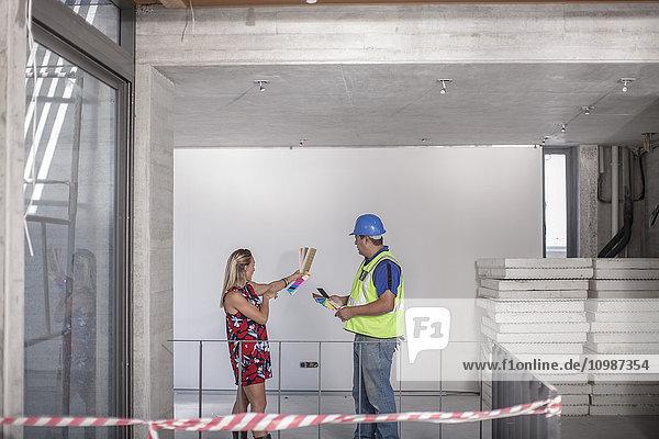 Bauarbeiter und Frau mit Farbmuster auf der Baustelle