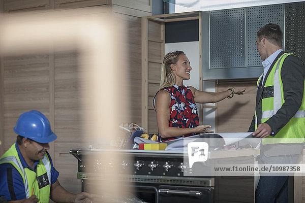 Architektin und Frau diskutieren über Kücheneinrichtung