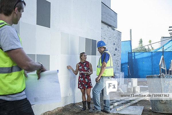 Bauarbeiter und Frau im Gespräch auf der Baustelle