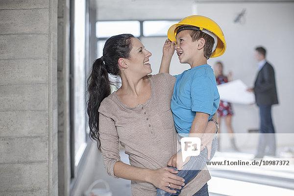 Mutter und Sohn mit Schutzhelm auf der Baustelle
