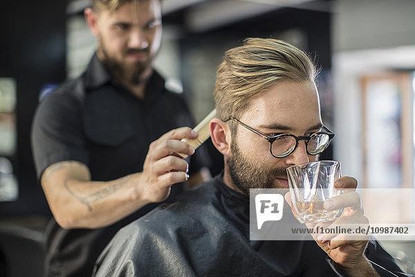 Friseur beim Kämmen der Haare eines Kunden