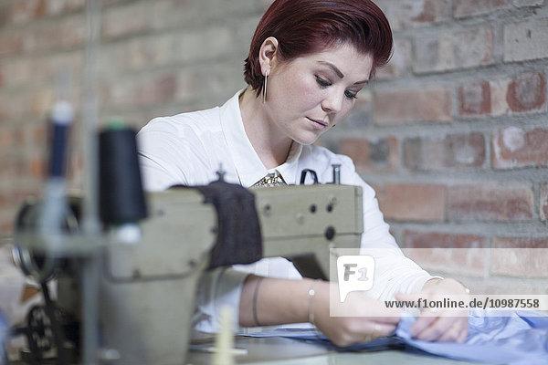 Junge Frau  die an der Nähmaschine arbeitet