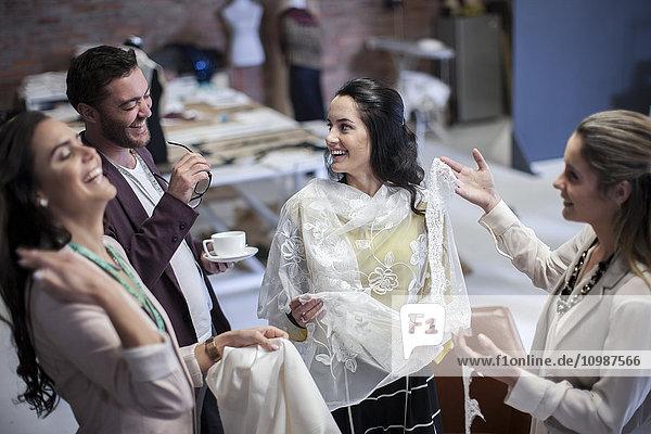 Fröhliche Schneiderinnen mit Kunden im Modeschauraum