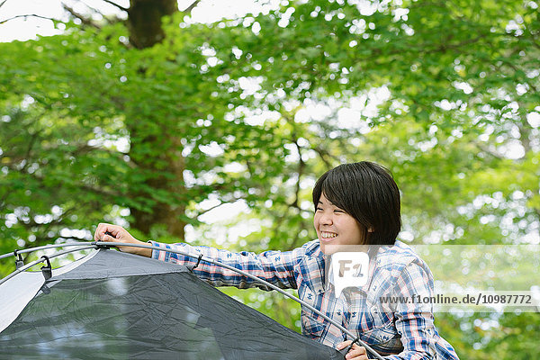 Young Japanese woman putting up a tent at a camp site
