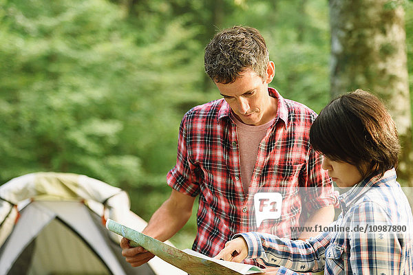 Friends checking map at a camp site