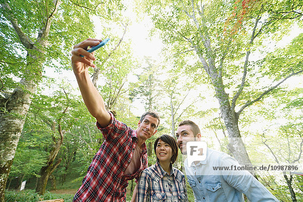 Multi-ethnic group of friends taking selfie at a camp site