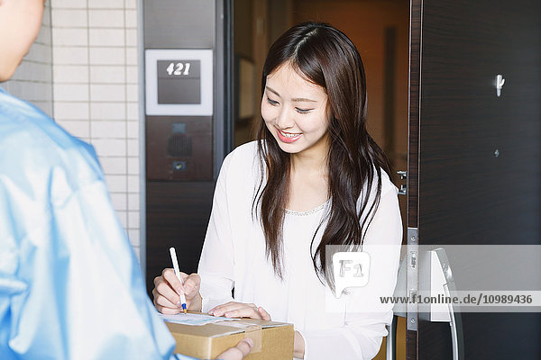 Young Japanese woman getting package from delivery man