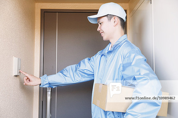 Young Japanese delivery man ringing doorbell