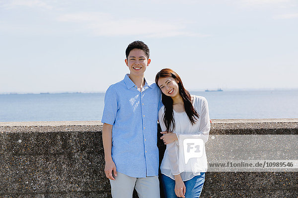 Young Japanese couple leaning on concrete wall by the sea