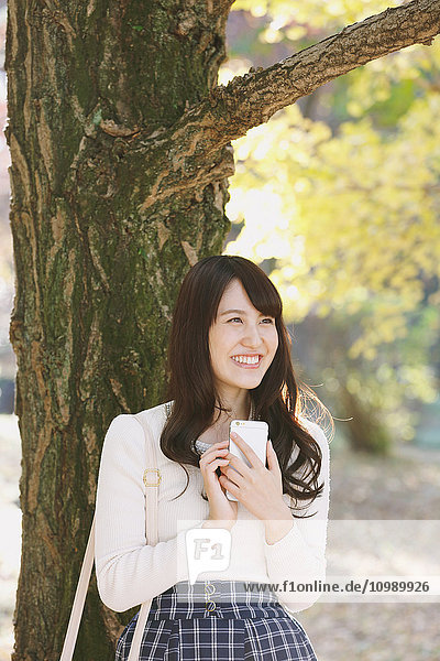 Young Japanese woman with smartphone in a city park