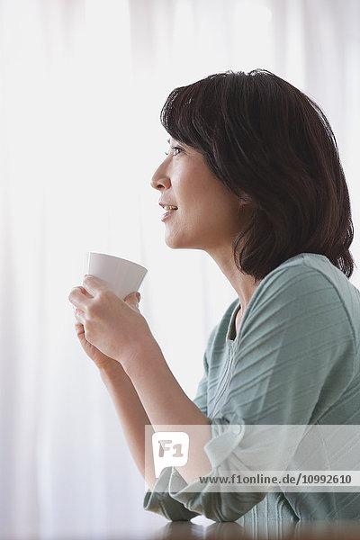 Senior Japanese woman having coffee in the living room