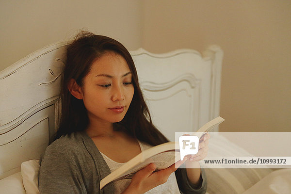 Young attractive Japanese woman reading in bed
