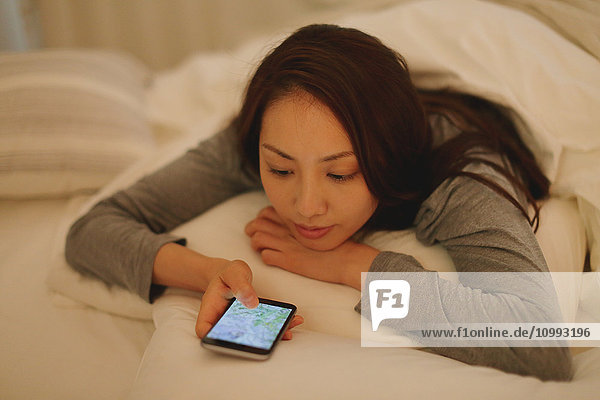 Young attractive Japanese woman with smartphone in bed