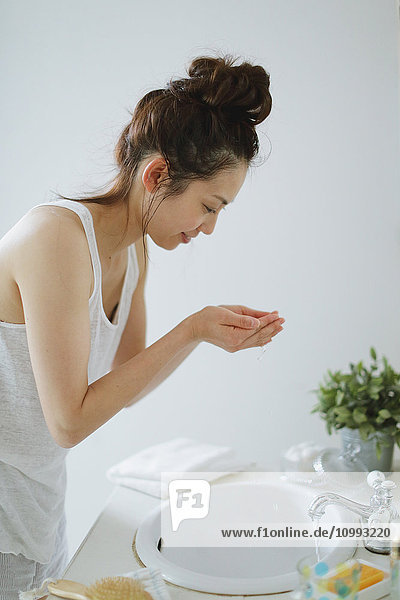 Young attractive Japanese woman washing face in the bathroom
