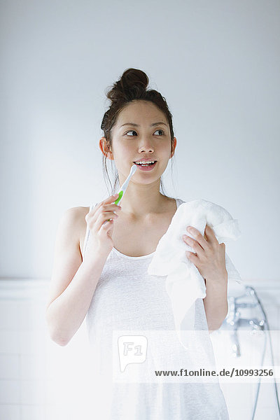 Young attractive Japanese woman brushing teeth in the bathroom